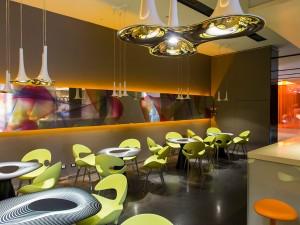 Rashid kombinierte die Leuchten 'Nafir' von Axo Light, die Hocker 'Kant' von Casamania, die Sitzmöbel 'KAT' von Redi und die Tische 'TAK' von Redi mit einer von HP gedruckten Grafik zu einem stylischen Gesamtinterieur. Foto: Giuseppe Creti