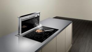 Bei Bedarf und via Berührung des touchControl Bedienfeldes fährt die Tischlüftung aus der Arbeitsplatte und saugt effizient Kochdünste ab. Foto: Siemens