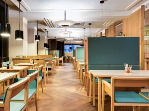 """""""Fine Dining"""" im Obergeschoss: Die eleganten Stühle und die omnipräsenten, klassischen Vierfußtische sorgen für Sitzfeeling. © ACTS/shm"""