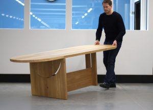 Einfach an den Rundungen angehoben, wird der stabile Holztisch mit seinem Rollen mobil und kann spielend leicht verschoben werden. © Tecta